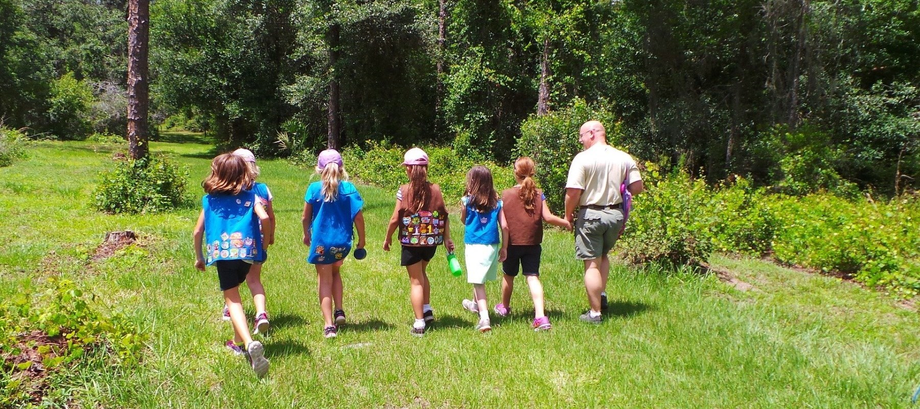 Girl scout club walking through forest with leader